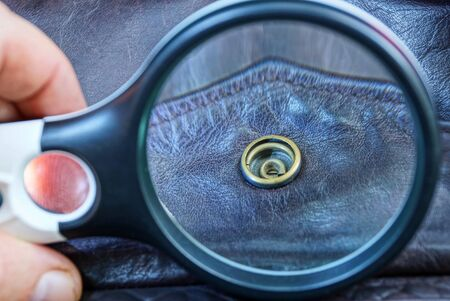 magnifier magnifies a rivet on brown leather clothes