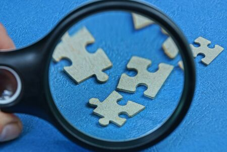 black magnifier increases gray paper puzzles on a blue table