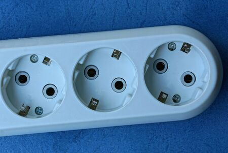 part of a white plastic extension cord with sockets