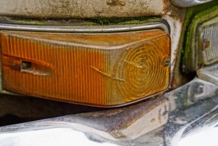 one dirty red light on an old car