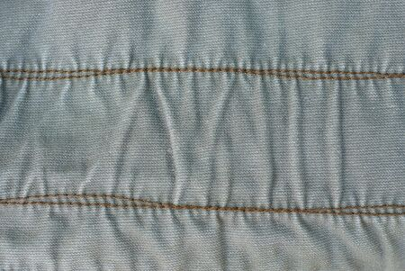 gray fabric texture of a piece of cotton clothing with a seam