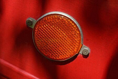 one red round plastic reflector on the metal wall of the trailer Stockfoto