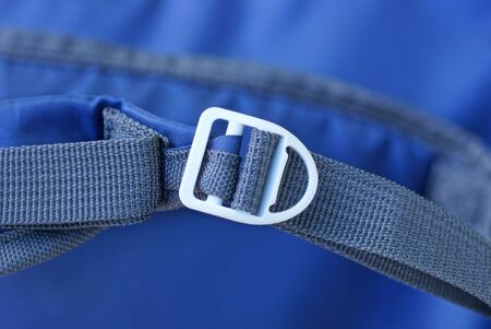 one white carabiner on a gray harness on a blue background Stockfoto