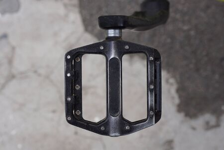 one black pedal on a bicycle on a background of gray asphalt