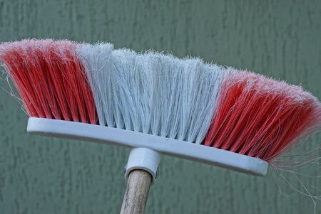 plastic broom with colored pile against a gray wall