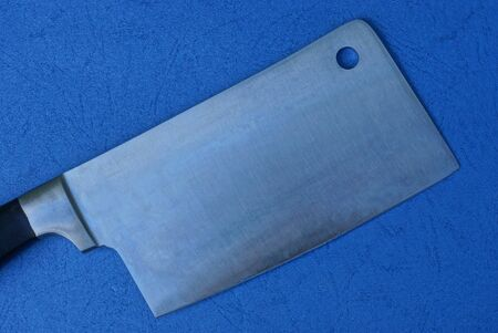 one big gray steel cleaver lies on a blue table