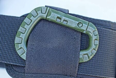 one large green plastic carabiner on a black harness made of fabric