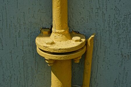 part of the yellow iron gas pipe on the gray wall of the building