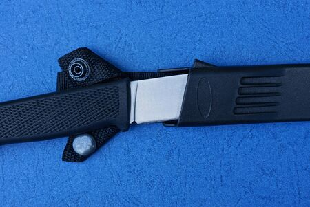 a knife in a black plastic case lies on a blue table Stockfoto
