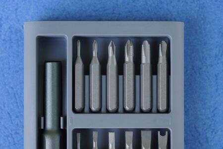 tool kit of gray metal bits for a screwdriver in a plastic box