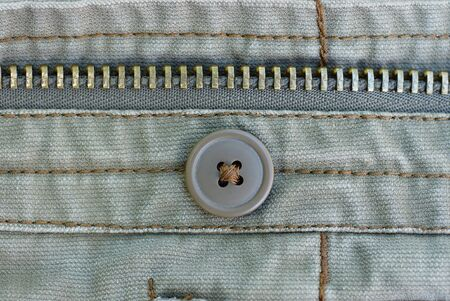 one brown button and metal zip on gray cotton clothes Stockfoto