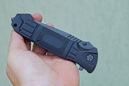 hand holds a one black folding knife on a gray background
