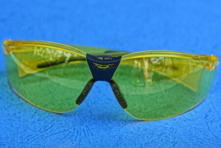one yellow sunglasses lie on a blue table