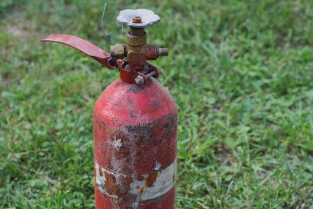 red old fire extinguisher with a valve on a background of green grass Stockfoto