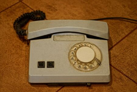 old gray plastic phone with a cord stands on a brown table