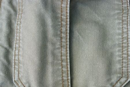 gray fabric background of a piece of cotton clothing with a seam