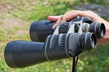 hand holds big black binoculars on the street against the background of green grass