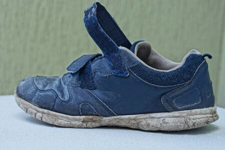 one old blue and dirty sneaker stands on a white table 版權商用圖片