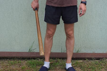 wooden bat in hand at the foot of a man in black shorts Stockfoto