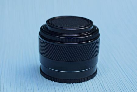 one camera lens closed by a black cap lies on a blue table
