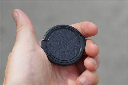 hand holds a black plastic lens cap on a gray background Stockfoto