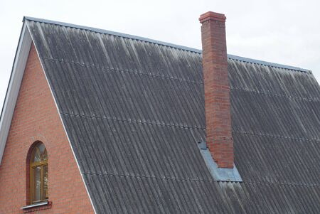 long brown brick chimney on a gray slate roof