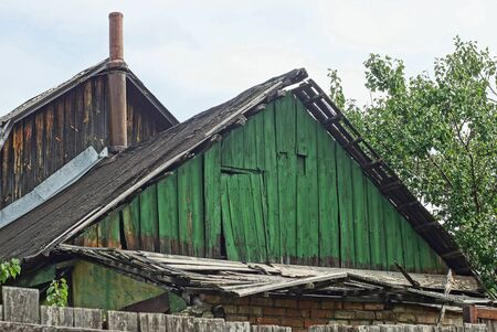 old green wooden loft with the door of a rural house on a background of sky