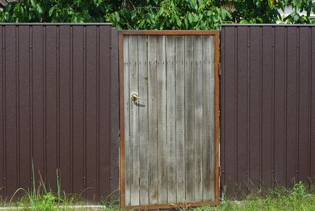 gray wooden door and brown metal fence on the street in green grass Stockfoto