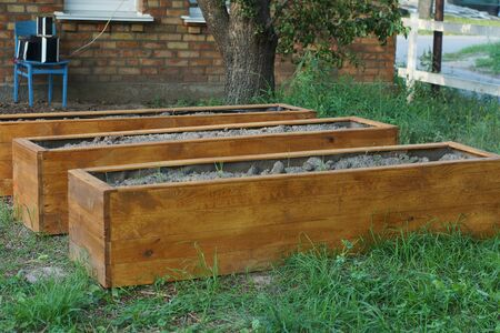 row of brown wooden crates with earth on green grass in the garden Stockfoto