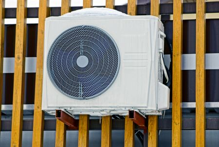 one gray air conditioner on a brown wooden wall in white snow Stok Fotoğraf