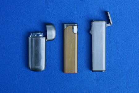 set of three old metal lighters on a blue table