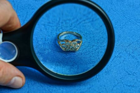 black magnifier in hand enlarges a gold ring with precious stones on a blue table