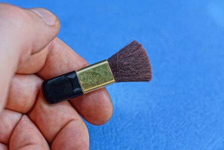 one small brown cosmetic brush lies on fingers on a blue background