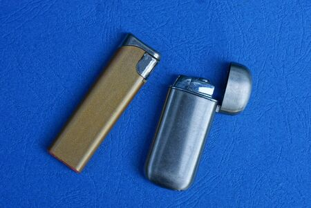 set of two old metal lighters on a blue table