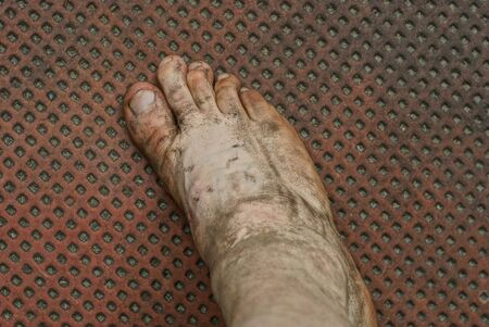 one bare foot in gray mud on a brown floor