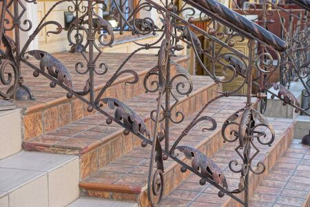 Staircase with concrete steps and iron brown handrails with a forged pattern near the wall