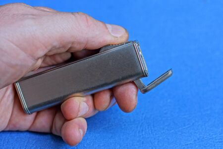 hand holds a gray metal lighter on a blue background