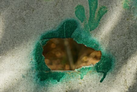 one big hole on a gray concrete wall in green paint Stok Fotoğraf