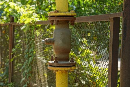 gray valve on a large iron pipe on fence a street