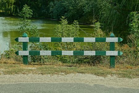 wooden striped barrier by an asphalt road on the shore of a forest lake