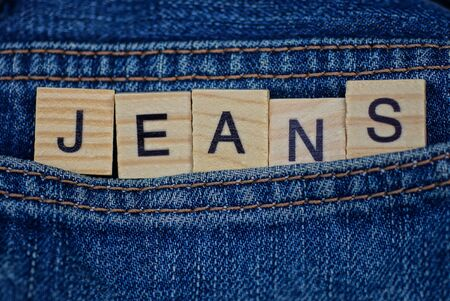 word jeans made of wooden letters on blue trouser fabric