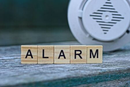 word alarm made of wooden letters and a plastic white annunciator Foto de archivo
