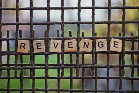 the word revenge from wooden letters on a rusty brown metal grate Stock fotó