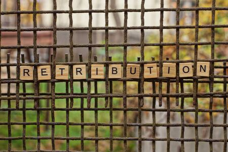 word retribution made of wooden letters on a rusty iron grate
