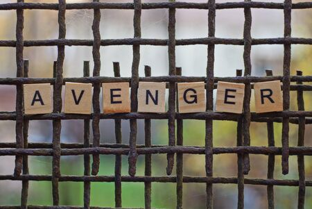 the word avenger from wooden letters on a rusty brown metal grate Stok Fotoğraf - 133056615