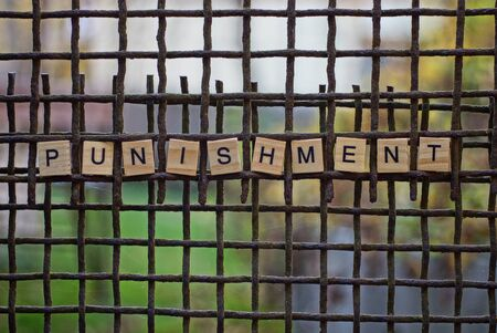 word punishment made of wooden letters on a rusty iron grate
