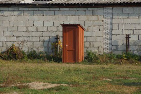 red wooden toilet in the street in green grass against a gray brick wall