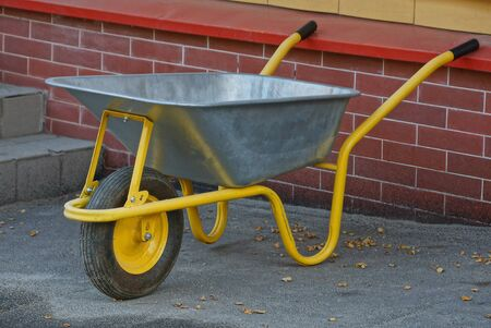 gray yellow metal wheelbarrow stands on the pavement near a brick wall