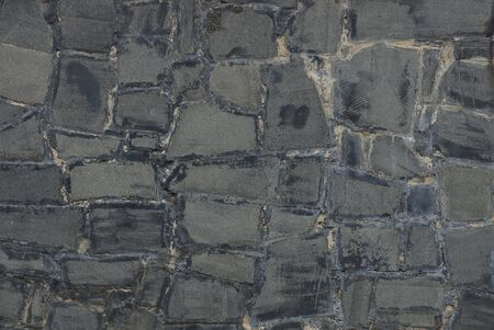 gray stone background of cobblestones and plaster in the wall