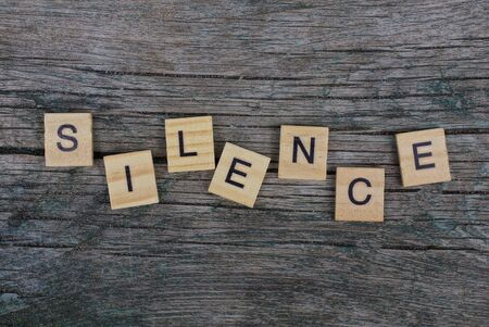 word silence from wooden letters on a gray table Stok Fotoğraf